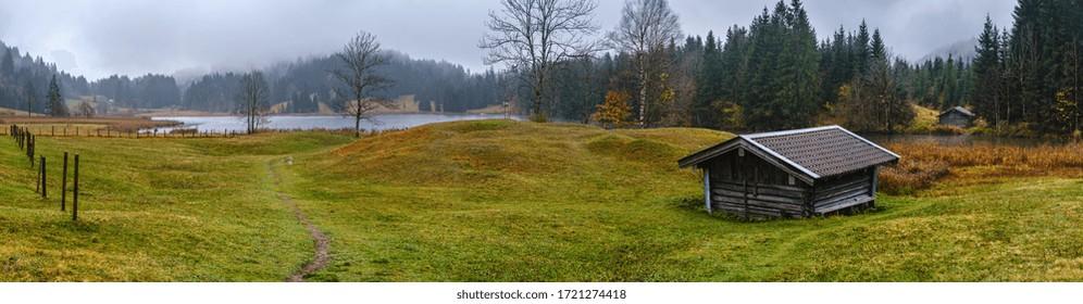 Alpensee Gerolde oder Wagenbruchsee, Bayern, Deutschland. Herbst bewölkt, neblig und tropfend Tag. Malerische Reisen, saisonale, wetterbedingte und landschaftliche Schönheitsszene.
