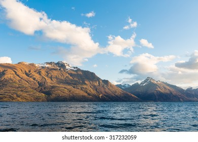 alpine and lake landscape with snow on top of the mountain