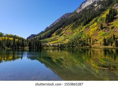 Alpine lake with mountain ridge reflection in autumn