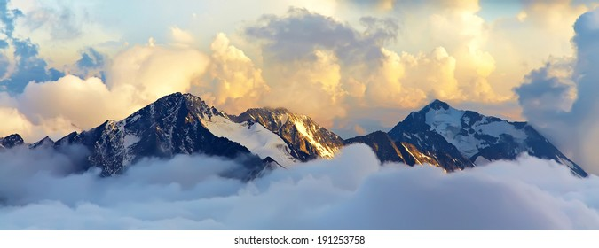 alpine landscape with peaks covered by snow and clouds. banner. panorama