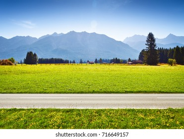 Alpine meadow and road, mountains on background. Landscape in sunny day