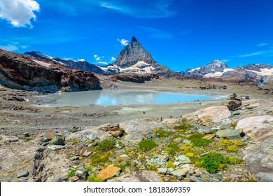 Alpine meadows around Matterhorn Peak or Mount Cervin o Monte Cervino and Swiss Alps reflected in glacier lake near Trockener Steg. Zermatt, famous mountain resort in Canton of Valais, Switzerland.