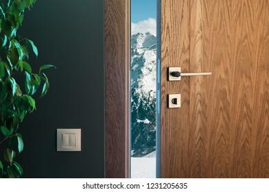 Alpine mountains behind a half-open door. Wooden door in a beautiful interior. Winter vacation thoughts