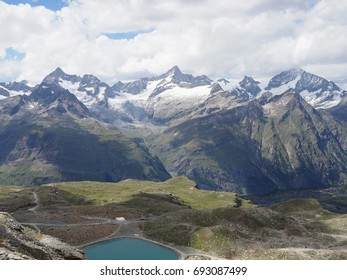 Alpine mountains range landscape and lake in swiss Alps at SWITZERLAND seen from Gornergrat near Zermatt village with cloudy blue sky in 2017 warm sunny summer day, Europe on July.