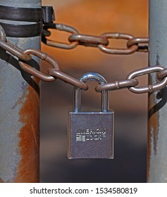 ALPINE, NEW JERSEY - OCTOBER 15, 2019: A silver colored American Lock company lock securing an opening in a chain linked fence. American Lock offers high-quality commercial safety solutions.