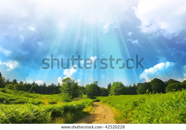 Alpine road in green pasture with blue sky and sun rays from above.