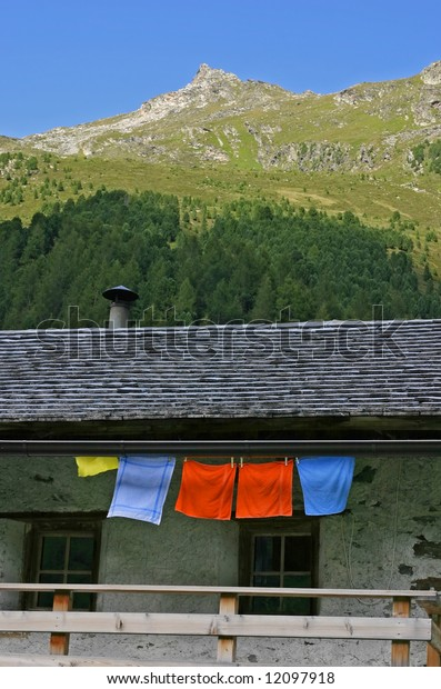 Alpine scenery with hut, mountain and colorful textiles