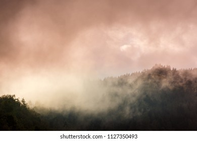 Alpine scenery with mist, fog and rain clouds, in summer
