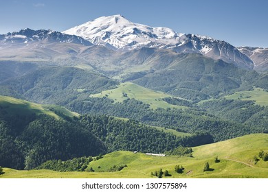 Alpine scenery with panoramic view of snow capped summit of Elbrus mount, the mountainside covered with forest and farm building in the valley on a sunny summer day. Karachay-Cherkessia, Russia