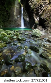 Alpine spring with romantic waterfall falling deep into a narrow gorge, forming a small green pond, lit by sunray, penetrating to the canyon. Pristine nature and geodiversity concept.