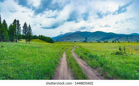 Alpine steppe in the background of snowy mountains. Road in Samakh steppe, Altai Mountains, Russia.