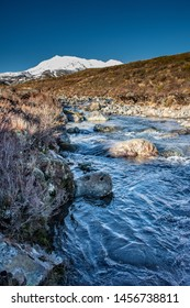 Alpine stream flows from the slopes of Mt Ruapehu in NZ through an autumn landscape