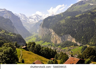 Alpine summer landscape with mountains, village Lauterbrunnen and Staubbach waterfall,  Joungfrau mountains on background,Bernese Oberland, Switzerland, Europe