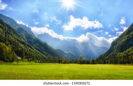 Alpine valley Logarska dolina, Slovenia, green pasture with forest and mountains in background, clouds on blue sky and sunstars for effect, outdoor tourism and travelling, warm and bright scene