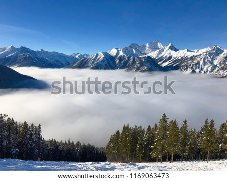 Alpine View With Clouds Below The Ski Snowboarding Hill In Canadian Rockies Panorama