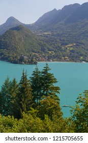Alpine view showing forests and mountains and the turquoise waters of Lake Annecy France