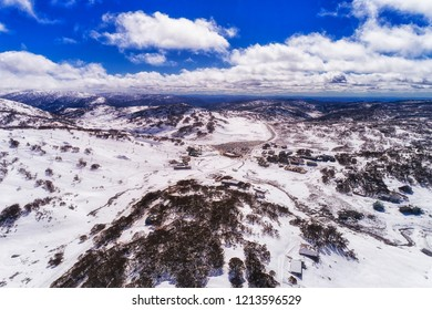 Alpine village Perisher valley in Snowy Mountains of Australia - aerial elevated view with snow covered slopes of popular skiing resort during height of winter skiing season.