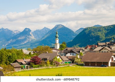 Alpine village St. Gilgen with a church, mountains on background. Summer landscape of countryside, Austria.