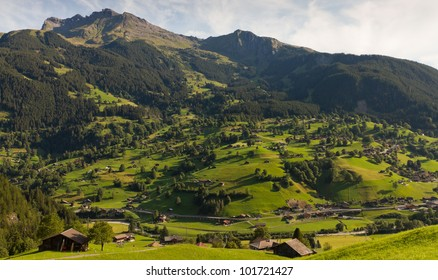 Alpine village with timber huts at late afternoon on mountain face, Valais Switzerland