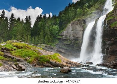 Alpine waterfall in mountain forest under blue sky.