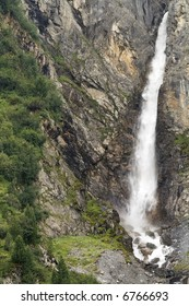 Alpine waterfall runs down mountains with trees