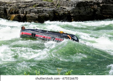 Alpine, Wyoming, USA June 26, 2016 A family clings to the side of an overturned rubber raft on the white water rapids of the snake river in western Wyoming.