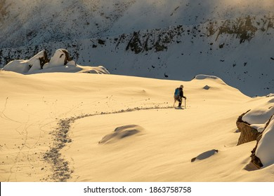 Alpinist alone exploring mountains at magical sunset in Swiss Alps, Switzerland