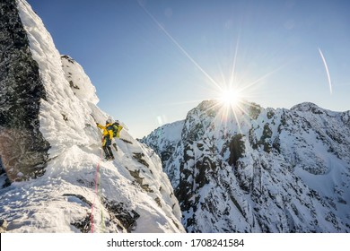 An alpinist climbing a steep ice, snow and rock face in alpine like mountain landscape of High Tatras, Slovakia. Winter extreme mountaineering and alpinism on alpine peaks. Sunset over a climber.