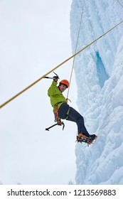 Alpinist man with ice tools axe in orange helmet climbing a lar