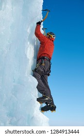 Alpinist man with ice tools axe climbing a large wall of ice. Outdoor Sports Portrait