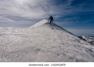 An alpinist on an adventure ascent of a high alpine peak. Climber or mountianer near the summit of a snow covered peak. Winter alpine landscape, extreme ascent, blue sky and sharp snow ridge.