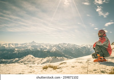 Alpinist on the mountain summit. Shot in backlight, stunning panoramic view of the alpine arc. Concept of success and conquering the top. Toned image, old retro touch.