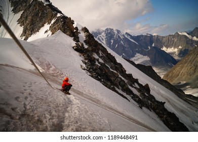 The alpinist sits on the slopes of the snow mountains. Belukha peak (4509 m) in Altai mountains. Siberia. Russian Federation.