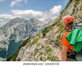 Alpinist wearing helmet looking at beautiful Slovenian mountains.