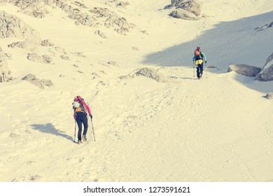 Alpinists ascending a snowy mountain slope with crampoons.