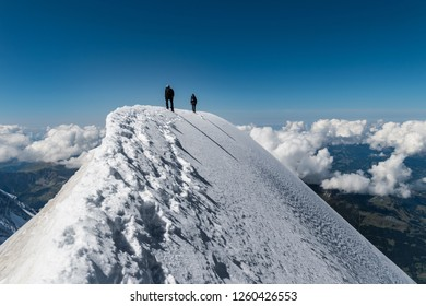 Alpinists on Aiguille de Bionnassay summit - extremely narrow snow ridge above clouds, Mont Blanc massif, France