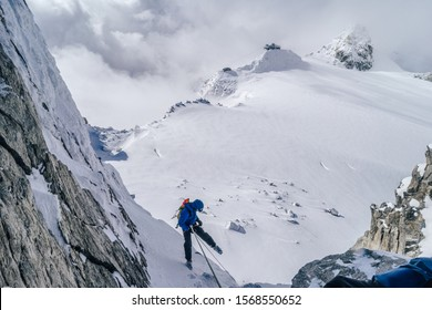 Alpinst rappeling down from a mountain. WInter alpine climbing on snow and rock. Abseiling on rope on a glacier, Mont Blanc Massif, France.