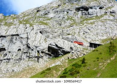 ALPNACHSTAD, SWITZERLAND - July 3, 2014: The Pilatus-Bahn, the world's steepest cogwheel railway with a car about to enter a tunnel on Mount Pilatus.