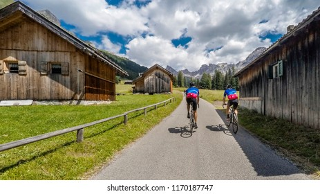 Alps, dolomites. Close up of Group of cyclists along a mountain road with mountain huts
