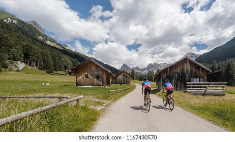 Alps, dolomites. Couple of male cyclists along a mountain road with mountain huts on the sides.