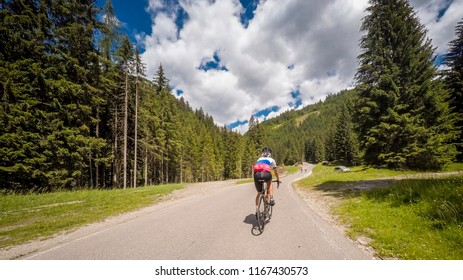 Alps, dolomites Cyclist girl along a mountain road in the woods