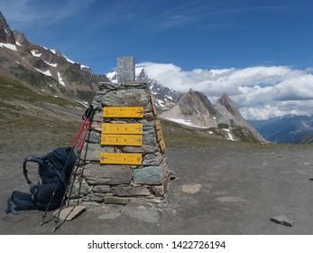 Alps, France, Tour du Mont Blanc -   Col de la Seigne pass with  tourist signposts, backpack and trekking poles