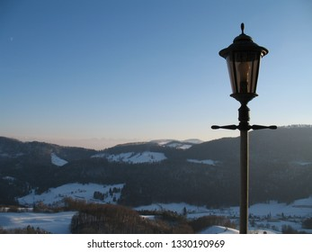 alps at horizon in winter with Street lantern in front of the Jura hills with blue sky. CH Switzerland