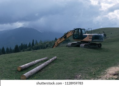 Alps Mountain Landscape. Excavator in the mountains