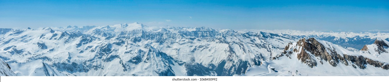 Alps mountains panorama in winter. Beautiful scenery of Tyrol Alps from peak Top of Salzburg, 3029m. Mountains with snow and blue sky. Panoramic view