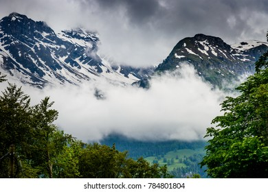 Alps Mountainscape in Switzerland with snowy pwaks partly covered by clouds and a small hamlet in the valley.