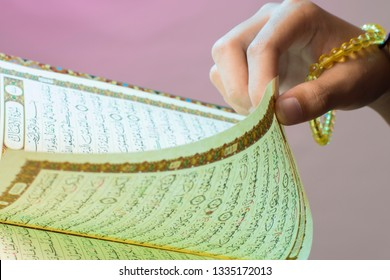 Al-Qur'an. Indonesia Muslim. Open Qur'an sheet by the hand holding the prayer beads (tasbih). The Qur'an is the holy book of Islam.
