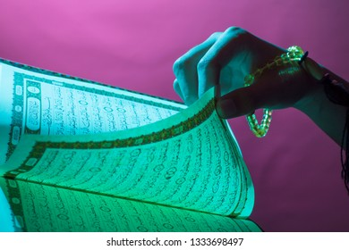Al-Qur'an in Jakarta, Indonesia. Open Qur'an sheet by the hand holding the prayer beads (tasbih). The Qur'an is the holy book of Islam.
