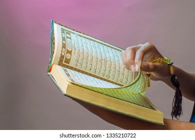Al-Qur'an. Open Qur'an sheet by the hand holding the prayer beads (tasbih). The Qur'an is the holy book of Islam.