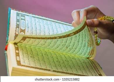 Al-Qur'an. Open Qur'an sheet by the hand of Indonesian muslim, holding the prayer beads (tasbih). The Qur'an is the holy book of Islam.